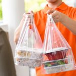 delivery-man-orange-uniform-delivering-asian-food-boxes-plastic-bags-woman-customer-home_8087-4356.jpg